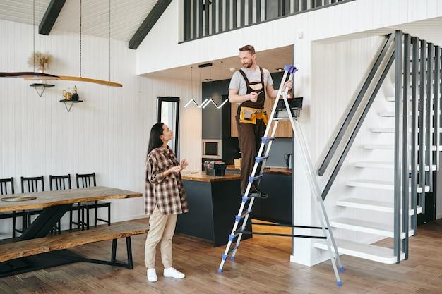 Giovane in uniforme in piedi su una scala in una stanza e parlando con una donna in abbigliamento casual