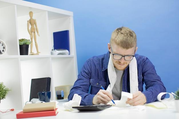 Giovane che per mezzo del calcolatore e delle ricevute di acquisto che gestiscono bilancio domestico da solo