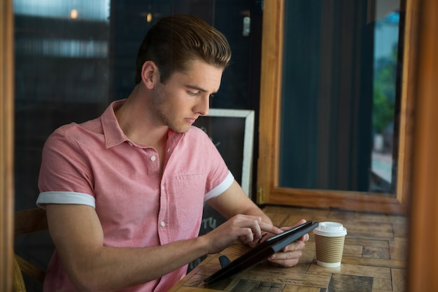 Giovane che per mezzo della compressa digitale al tavolo nella caffetteria