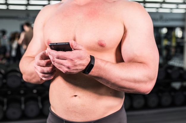 Giovane che utilizza il braccialetto di forma fisica durante l'allenamento sportivo in palestra