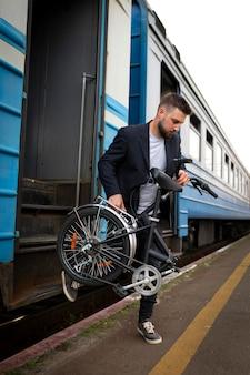 Giovane che utilizza una bicicletta pieghevole mentre viaggia in treno