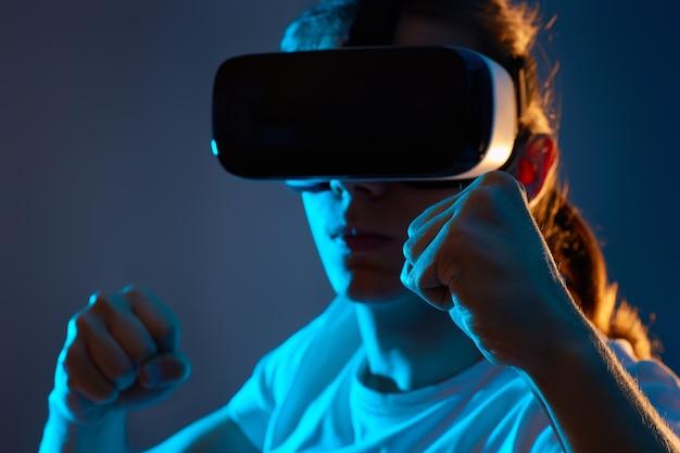 Giovane che utilizza occhiali di realtà virtuale su sfondo blu scuro. concentrarsi sulla mano