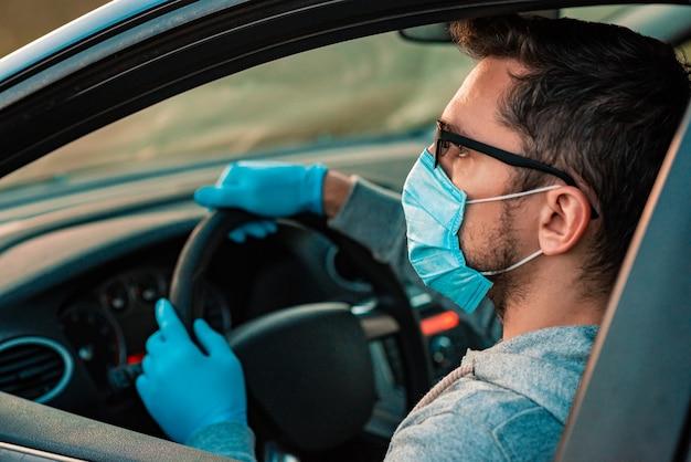 Giovane che usa disinfettante per le mani o gel alcolico per lavarsi le mani in macchina. autista in maschera protettiva e guanti. pandemia di coronavirus. quarantena.
