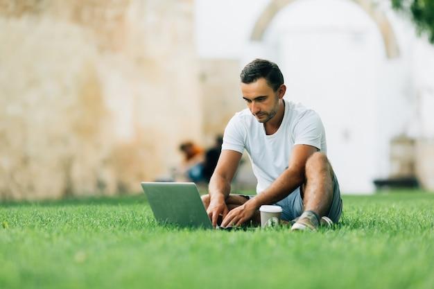 Giovane che usa il suo computer portatile sull'erba nel parco cittadino estivo