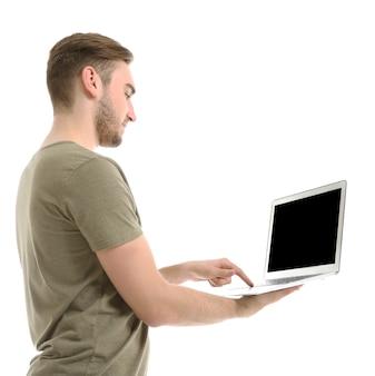 Giovane che per mezzo del computer portatile, isolato su bianco
