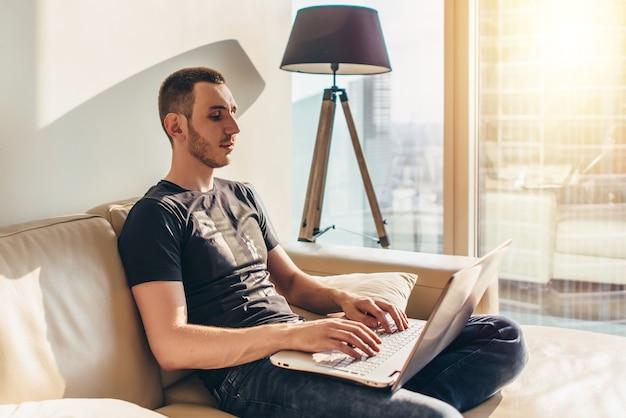 Giovane che usa il laptop mentre è seduto su un divano