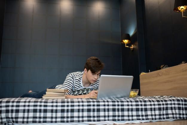 Giovane che per mezzo del computer portatile e scrivendo a letto