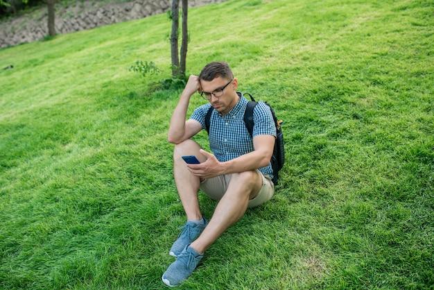 Giovane che utilizza il telefono cellulare sul parco cittadino autunnale.