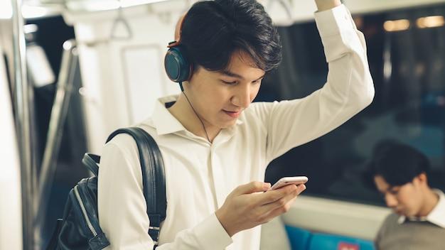 Giovane che utilizza il telefono cellulare sul treno pubblico