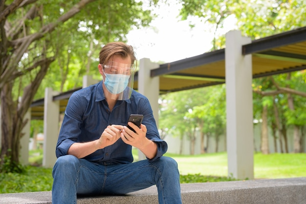 Giovane che utilizza il telefono con maschera e visiera mentre è seduto al parco