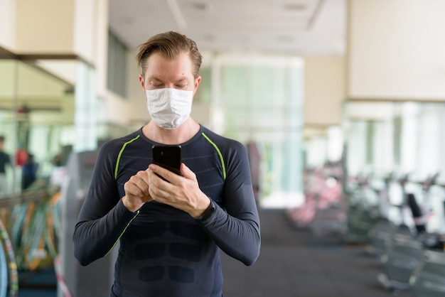 Giovane che utilizza il telefono con maschera per la protezione dall'epidemia di coronavirus in palestra durante il coronavirus covid-19