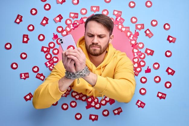Giovane uomo utilizzando smart phone, ossessionato da internet. bel ragazzo caucasico in abbigliamento casual tra i molti mi piace