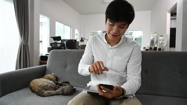 Giovane uomo utilizzando smart phone mentre è seduto con il suo gatto sul divano di casa.