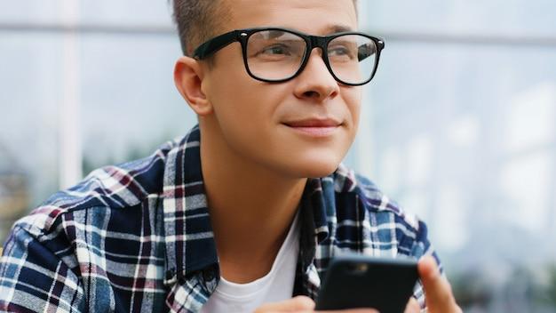 Giovane che per mezzo dello smartphone e guardando al lato. tecnologia e connessione
