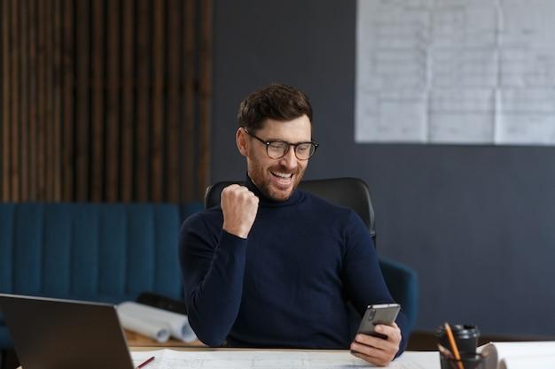 Giovane che utilizza smartphone e sorridente uomo d'affari felice utilizzando app per telefoni cellulari che inviano messaggi di testo al fratello...