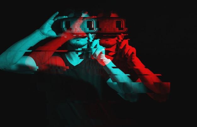 Giovane che per mezzo della cuffia avricolare di vetro di realtà virtuale di vr