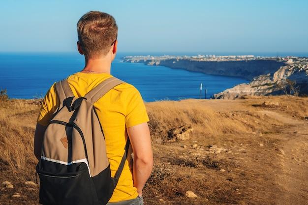 Giovane uomo in vacanza sul bordo della scogliera di cape fiolent in crimea