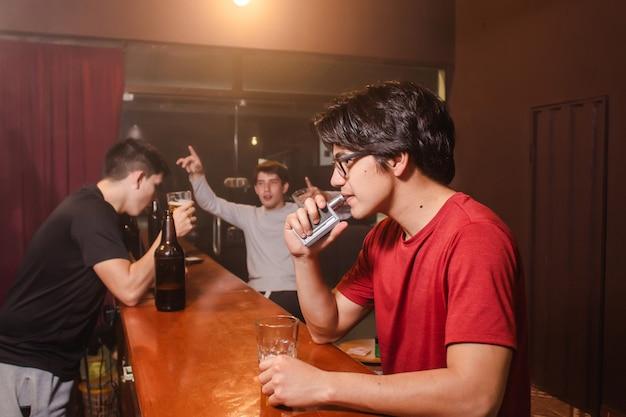 Un giovane che svapa con i suoi amici ubriachi al bar.