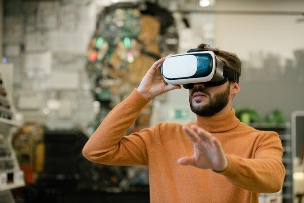 Giovane uomo in cuffia da realtà virtuale che allunga il braccio stando in piedi davanti al display e toccandolo