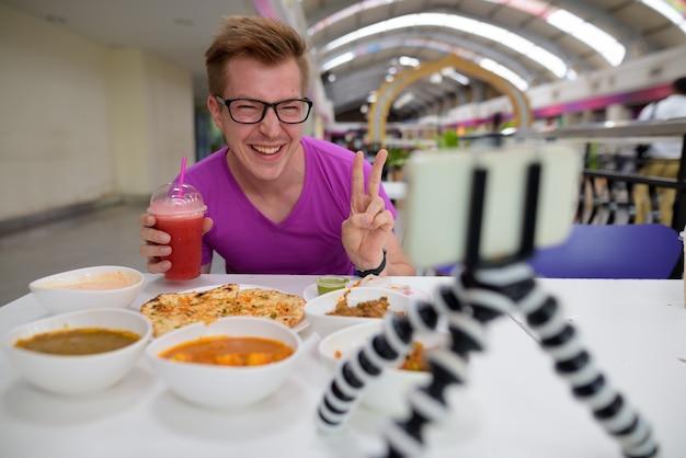 Giovane uomo vlogging con il telefono cellulare nel ristorante indiano