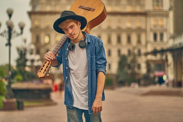 Giovane uomo a piedi in strada con la chitarra