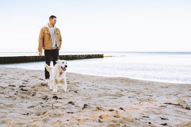 Il giovane cammina con il suo golden retriever in riva al mare al giorno d'autunno.