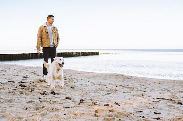 Il giovane cammina con il suo golden retriever in riva al mare al giorno d'autunno