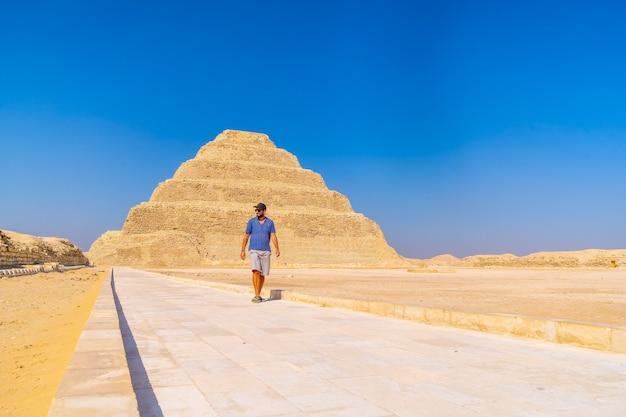 Un giovane uomo che cammina nella piramide a gradini di djoser, saqqara. egitto. la necropoli più importante di menfi. la prima piramide al mondo