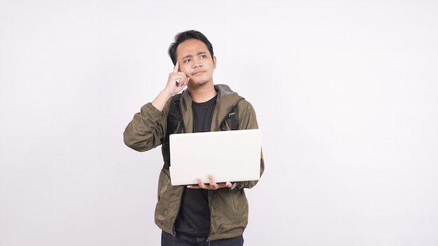 Il giovane indossava una borsa mentre pensava a uno spazio bianco con il laptop