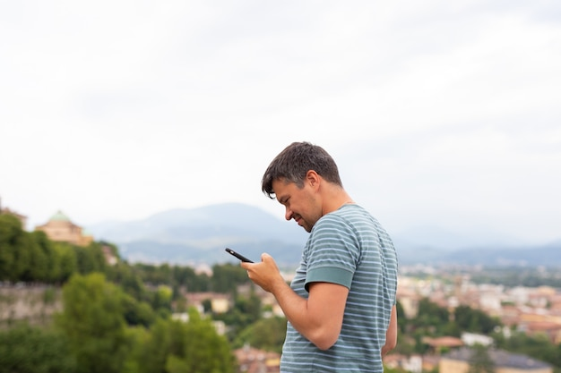 Il giovane guarda navigare in internet detiene sembra smart phone mobile in una città. concetto di viaggio. viaggiatore. vacanze estive.