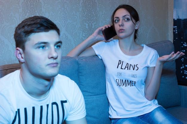 Giovane che guarda la televisione o gioca a un videogioco mentre la sua ragazza parla al telefono seduta sul divano davanti a una tv a casa in un'atmosfera rilassata