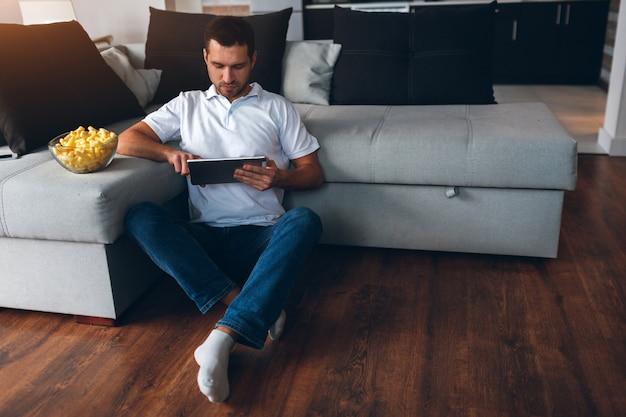 Giovane che guarda la tv nel suo appartamento. guardare film o programma. siediti sul pavimento e usa il tablet.