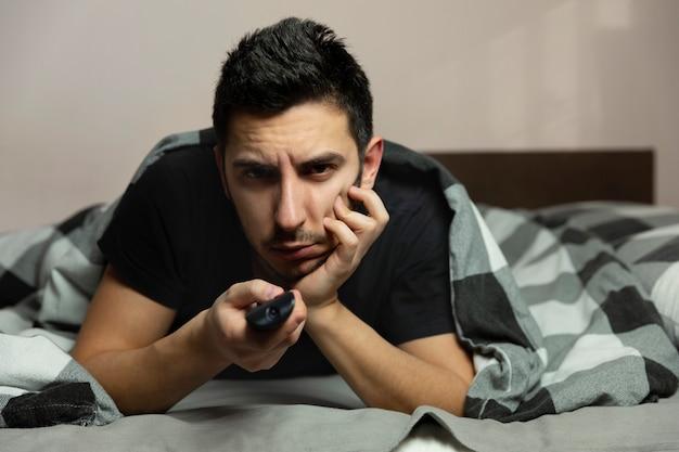 Un giovane che guarda la tv mentre giace su un divano.