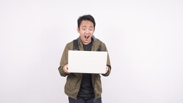 Il giovane che indossa la borsa che grida e urla su uno spazio bianco con il computer portatile