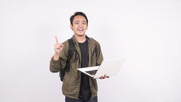 Il giovane uomo che indossa la borsa su uno spazio bianco che punta laptop