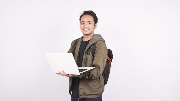 Il giovane che indossa la borsa su uno spazio bianco con il computer portatile