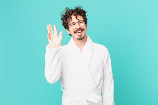 Giovane uomo che indossa accappatoio sorridendo felicemente, agitando la mano, dando il benvenuto e salutandoti