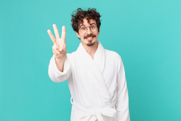 Giovane uomo che indossa accappatoio sorridente e sembra amichevole, mostrando il numero tre