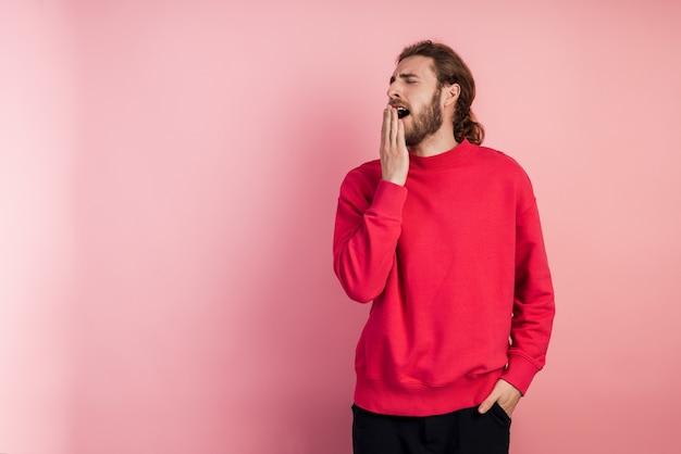 Giovane uomo che indossa casual t-shirt in piedi. annoiato, sbadigliando stancamente si copre la bocca con la mano.