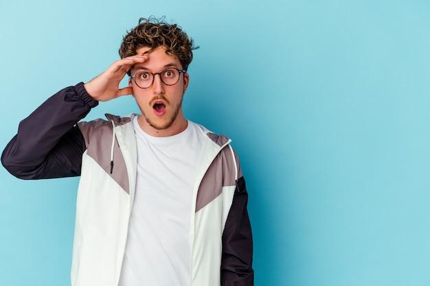 Giovane uomo che indossa occhiali isolati sulla parete blu che guarda lontano tenendo la mano sulla fronte