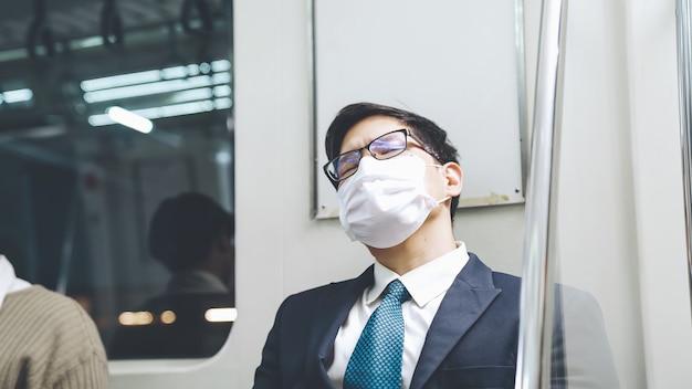 Il giovane che indossa la maschera per il viso viaggia su un treno della metropolitana affollato