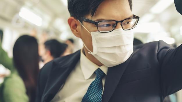 Giovane uomo che indossa la maschera per il viso viaggia sul treno della metropolitana affollato