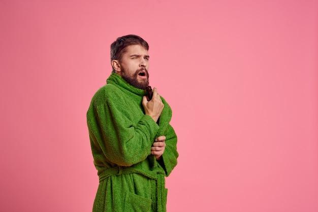 Giovane uomo che indossa una veste verde isolato