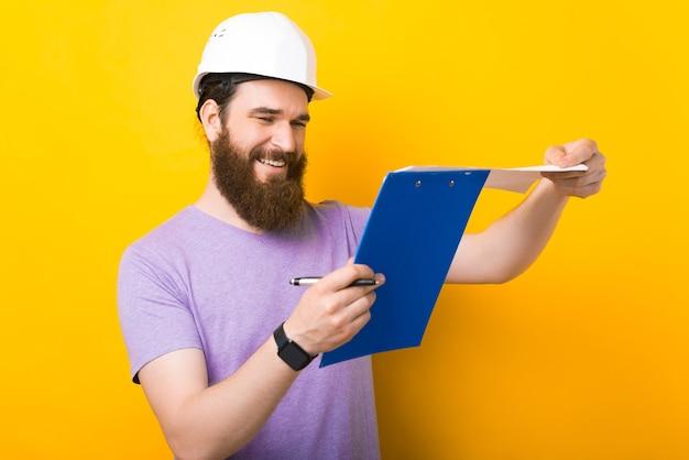 Il giovane che indossa il cappello di protezione dura sta scrivendo qualcosa su un cartone.