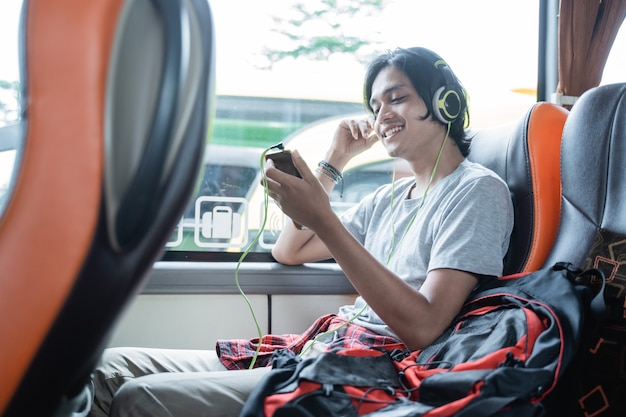 Un giovane uomo che indossa le cuffie mentre ascolta la musica da un handphone mentre è seduto vicino alla finestra durante un viaggio in autobus
