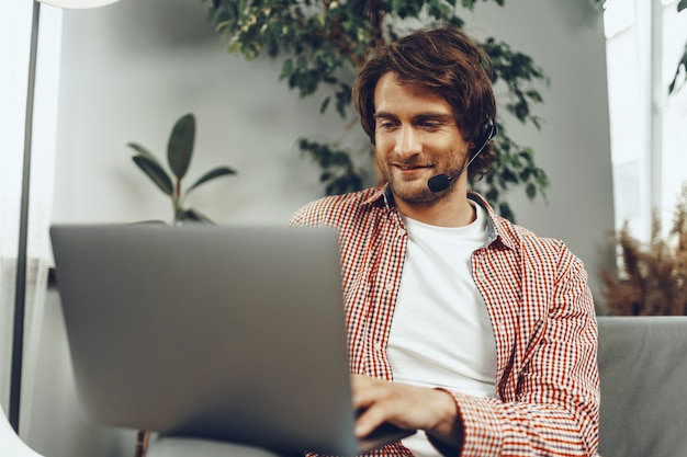 Giovane che indossa la cuffia avricolare facendo una videochiamata dal laptop