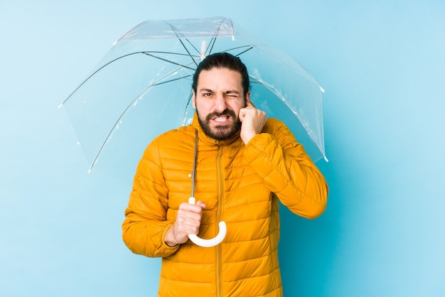 Giovane che indossa uno sguardo di capelli lunghi che tiene un ombrello isolato che copre le orecchie con le mani.