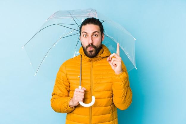 Giovane che indossa uno sguardo di capelli lunghi che tiene un ombrello isolato avendo qualche grande idea, il concetto di creatività.