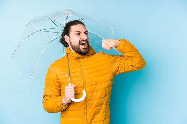 Giovane che porta uno sguardo di capelli lunghi che tiene un pugno di sollevamento isolato dell'ombrello dopo una vittoria, concetto del vincitore