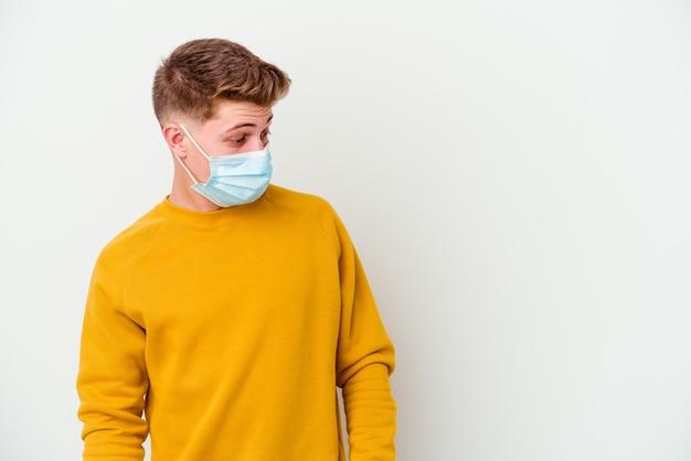 Il giovane che indossa una maschera per il coronavirus isolato su sfondo bianco è scioccato a causa di qualcosa che ha visto.